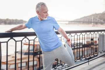 Warm up firstly. Concentrated unshaken strong man standing on the quay holding by the railings and stretching his leg.