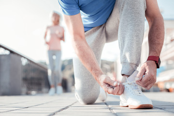 Is under control. Aged attentive sporting man having morning exercises standing on the knee and lacing up.