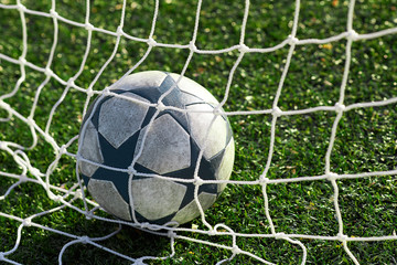 A modern soccer ball at the gate behind the net.