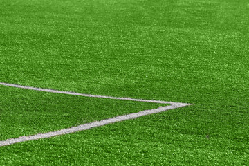 A close-up of an artificial green football turf with a corner marking at the gate.