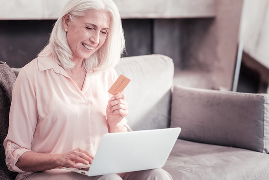 Easy to pay. Clever senior satisfied woman sitting in the bright room on the sofa using the laptop and holding credit card.