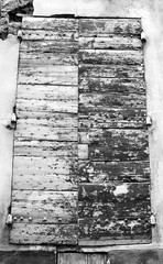 Closed wooden shutters with peeling paint and nail heads. Stucco wall house. Black and white.