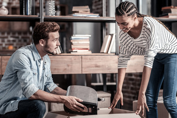Where to put it. Nice young positive man holding a toaster and looking at his girlfriend while packing things together with her