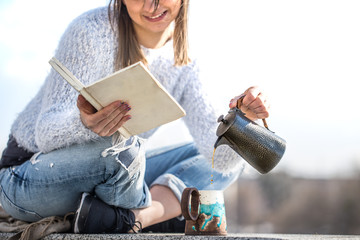 girl drinks coffee and reads book outdoors
