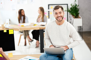selective focus of smiling marketing manager with laptop sitting on table in office