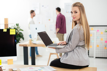 selective focus of young businesswoman with laptop looking at camera in office