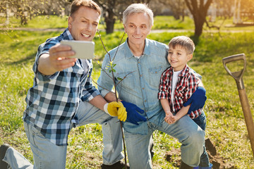 Friendly family. Cheerful delighted adult man holding a smart phone and making photos with his positive father and little son while spending time together