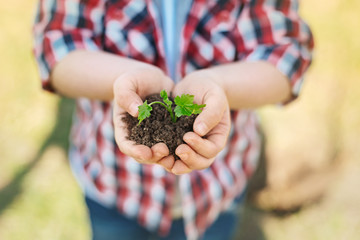 Caring hands. Close up of a pleasant boy holding handful of soil while expressing love for nature