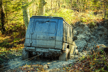Dirty offroad car stuck in dirt on sunny autumn day