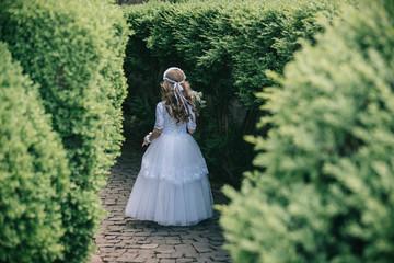 little bridesmaid standing in a green garden