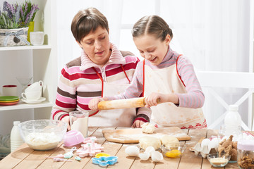 Mother and daughter cooking at home, making the dough for buns