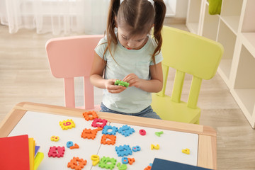 Cute little girl playing with figures while doing homework indoors
