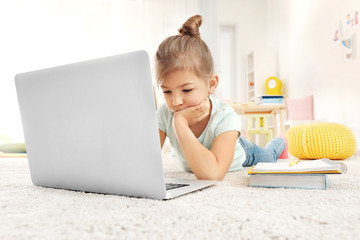 Cute little girl using laptop while doing homework indoors