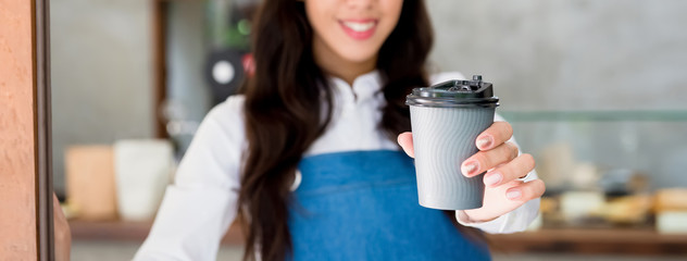 Young female cafe staff giving takeaway coffe cup