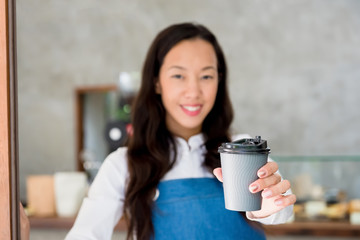 Aasian female staff giving takeaway coffe cup to customer at cafe
