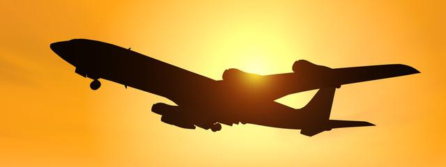 Silhouette eines Verkehrsflugzeuges vor gelbem Himmel