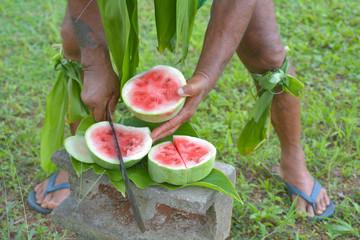 Cook islander cuts watermelon with long sharp knife in Rarotonga Cook Islands