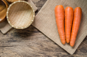 top view of raw carrot on sack cloth and  wooden utensil with copy space. organic healthy food concept.