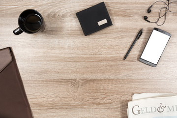 wooden desk with smartphone, headphones, pen, wallet, coffee mug, briefcase and newspaper