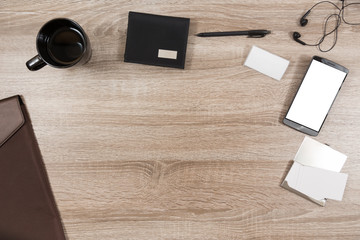 wooden desk with smartphone, headphones, pen, name tag, wallet, briefcase and business cards in a metal case