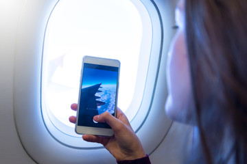 Young woman using mobile smartphone, take a photo on  airplane .porthole