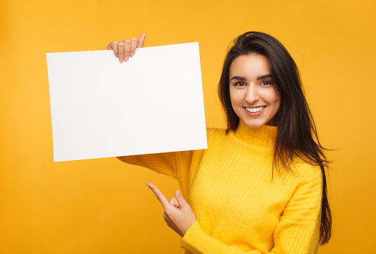 Charming brunette pointing at blank paper