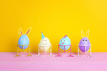 Funny Easter eggs with faces on bird legs on yellow background.