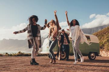 Friends dancing outdoors on roadtrip