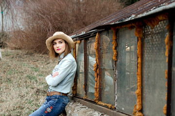 Woman in western wear in cowboy hat, jeans and cowboy boots.