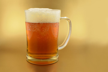 Beer glass with handle stock images. Glass with beer on a golden background. Beer on a golden background with copy space for text. Festive golden background