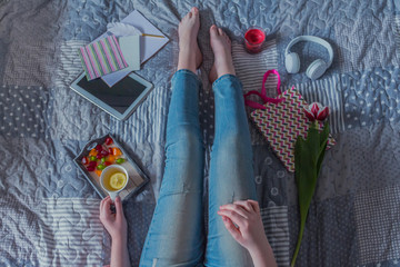 Beautiful Legs close-up in Bed. Woman is Drinking Tea . Girl Sitting on a Bed in Woolen Socks. Beautiful Woman no Face and Legs. Attractive Model Wears Woolen white Socks