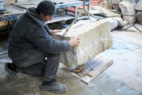 Sculptor gem-worker lifts a crane a piece of marble.