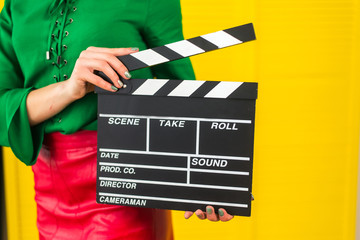 Attractive woman with a clapperboard in her arms