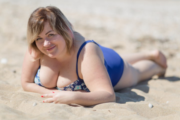 Overweight woman in blue one-piece swimsuit lying on sand
