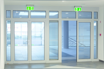 modern white office corridor with glass doors