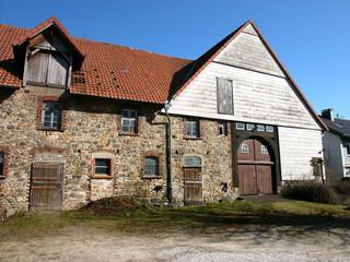 Altes Bauernhaus mit Mauerwerk aus Naturstein auf dem Lande in Heidenoldendorf bei Detmold in Ostwestfalen-Lippe bei Sonnenschein