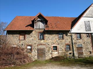 Schönes altes Gehöft mit alten Stallungen aus Naturstein vor blauem Himmel in Heidenoldendorf bei Detmold im schönen Ostwestfalen-Lippe
