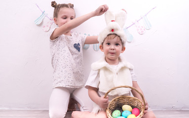 Brother and sister celebrate Easter. The boy is dressed in a rabbit costume and holds a korunzku with Easter eggs.
