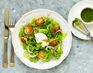 Spring salad with poached egg and crispy croutons. View from above.