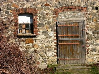 Altes Sprossenfenster und alte Holztür mit Patina in der Fassade aus Naturstein eines Bauernhaus in Heidenoldendorf bei Detmold in Ostwestfalen-Lippe bei Sonnenschein