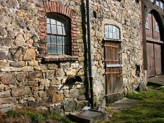 Wunderschönes altes Mauerwerk aus Bruchstein und Naturstein eines alten Bauernhaus mit Holztür in Heidenoldendorf bei Detmold in Ostwestfalen-Lippe