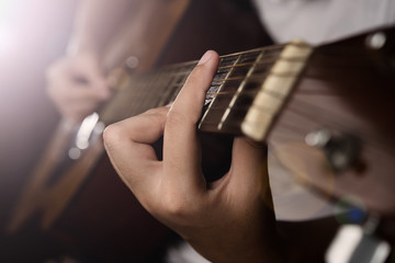 Hands playing acoustic guitar with finger catching chord on bar on night bokeh blur background
