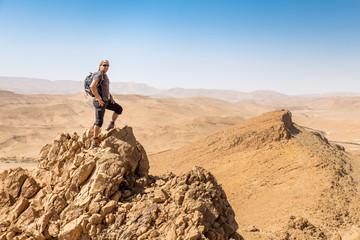 Backpacker tourist standing desert mountain cliff ridge edge landscape.