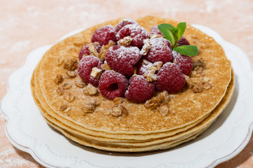 traditional thin pancakes with fresh raspberries on plate, closeup