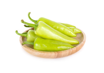 fresh green chili peppers with stem in wooden plate on white background