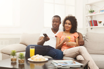 Happy african-american couple watching TV at home