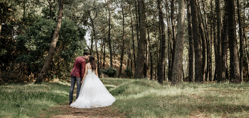 Back view of bride and groom kissing in forest