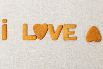 Edible volumetric letters word Love from biscuits with ginger on canvas. Crumbly Shortbread in the form heart.