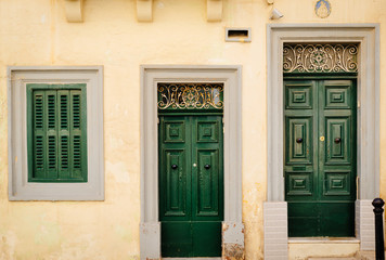 Facade of traditional maltese house in Valletta with beautiful green doors, Malta