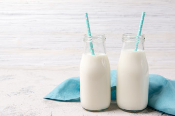 Two bottles of milk with blue straws on wooden background